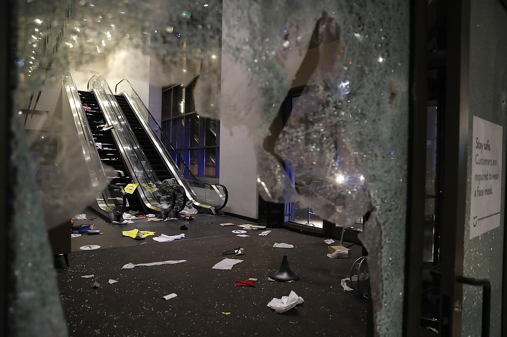 Glass is shattered in the Nordstrom store after a riot occurred in the Gold Coast area of the city early in the morning of Monday, Aug. 10, 2020 in Chicago.  Hundreds of people smashed windows, stole from stores and clashed with police in Chicago's Magnificent Mile shopping district and other parts of the city's downtown. (Jose M. Osorio /Chicago Tribune via AP)