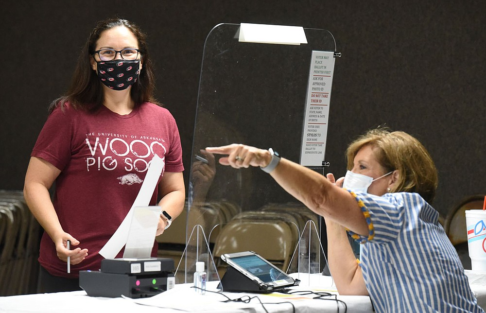 Washington County poll worker Paula Hand (right) assists Jeromie Hale Ivester with her ballot and collect her individually wrapped stylus before voting Tuesday, August 11, 2020, at the Rodeo Community Center in Springdale. Voters in Springdale and Bethel Heights went to the polls to decide whether to annex Bethel Heights into Springdale. Residents proposed the annexation to resolve the issue of Bethel Heights' failing sewer system. Check out nwaonline.com/200812Daily/ and nwadg.com/photos for a photo gallery. (NWA Democrat-Gazette/David Gottschalk)