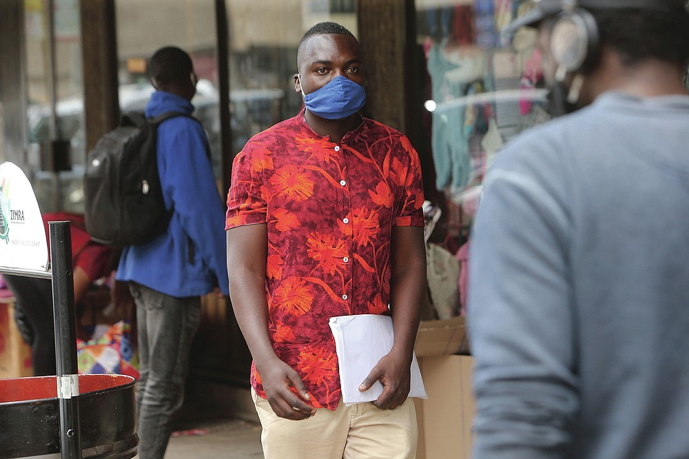 Emmanuel Reyai walks on the streets of Harare while looking for a job, Wednesday, Aug, 5, 2020. Around the world, young people armed with new degrees, diplomas and professional qualifications are struggling to enter the workforce as the pandemic pushes the global economy into recession. Two years after graduating with from Zimbabwe's Midlands State University, 24-year old Emmanuel Reyai is no closer to his goal of getting a job related to his degree in local governance. His search is stymied by both the African country's economic collapse and the coronavirus outbreak. (AP Photo/Tsvangirayi Mukwazhi)