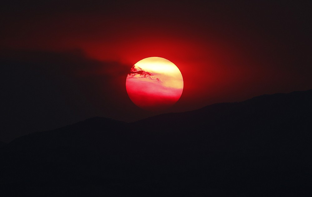 As wildfires burn throughout the Western Slope, the sun sets a bright orange behind the Rocky Mountains for residents of the eastern plains Wednesday, Aug. 12, 2020, in Denver. Forecasters predict the warm weather will persist, vexing firefighters as they deal with the wildland blazes. (AP Photo/David Zalubowski)