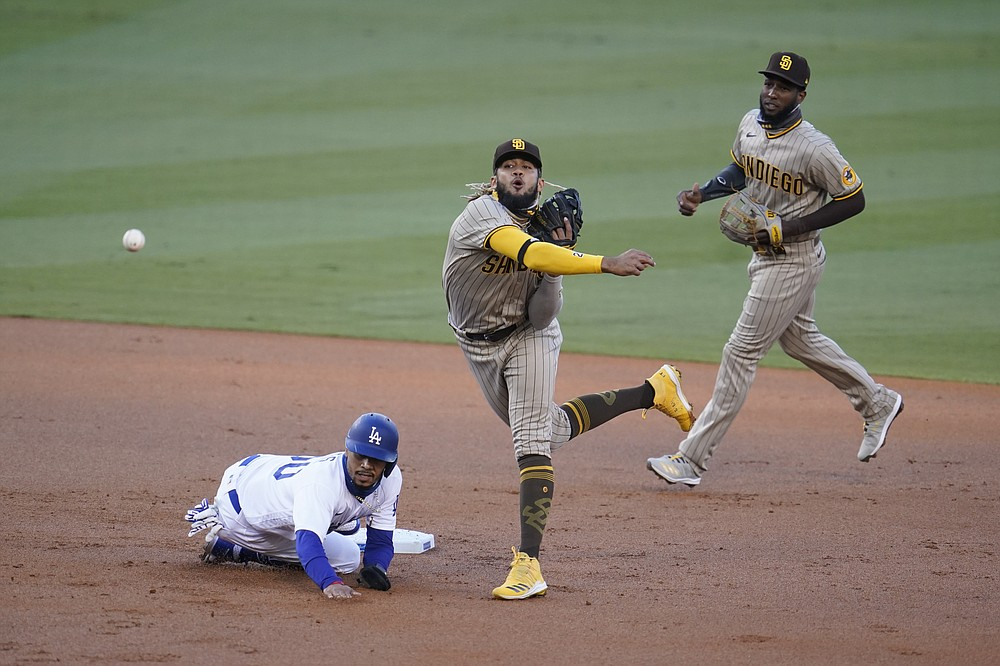 San Diego Padres shortstop Fernando Tatis Jr., center, completes a double play over Los Angeles Dodgers' Mookie Betts, left, on a ground ball from Cody Bellinger during the first inning of a baseball game Wednesday, Aug. 12, 2020, in Los Angeles. (AP Photo/Marcio Jose Sanchez)