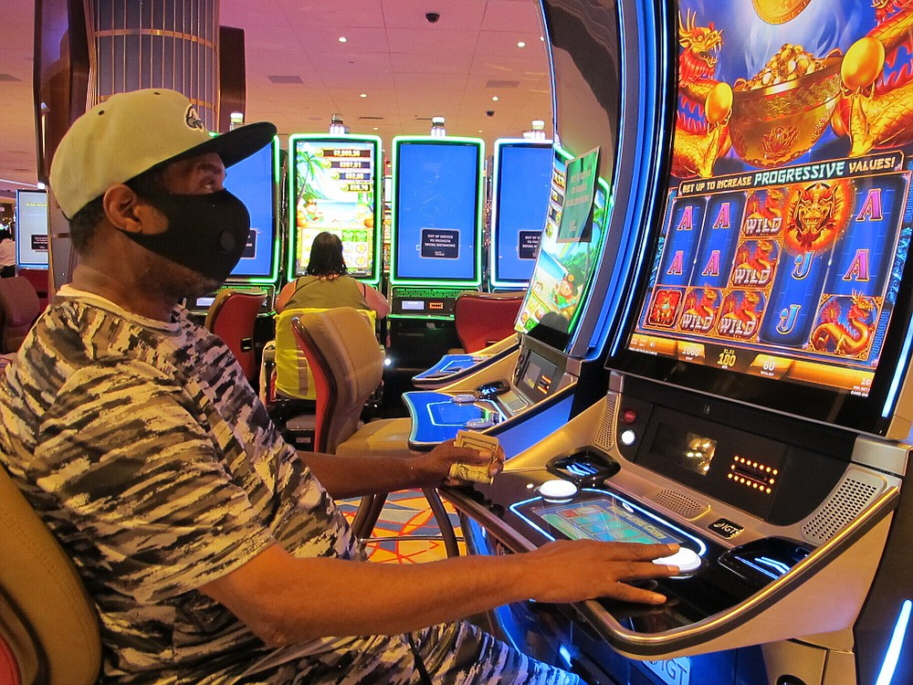 Seorang penjudi memainkan mesin slot di Hard Rock Casino di Atlantic City N.J. pada 2 Juli 2020, hari kasino dibuka kembali di tengah wabah virus korona. Kasino dan trek kuda New Jersey memenangkan $ 264,5 juta pada bulan Juli, angka yang turun hampir 21% dari tahun lalu, tetapi rumah judi dengan senang hati akan mengambil setelah berbulan-bulan tidak aktif. (Foto AP / Wayne Parry)