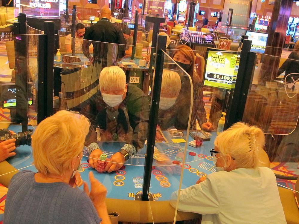 Seorang dealer memberikan setumpuk chip ke penjudi yang menang di kasino Hard Rock di Atlantic City, N.J. pada 2 Juli 2020, hari kasino dibuka kembali di tengah wabah virus corona. Kasino dan trek kuda New Jersey memenangkan $ 264,5 juta pada bulan Juli, angka yang turun hampir 21% dari tahun lalu, tetapi rumah judi dengan senang hati akan mengambil setelah berbulan-bulan tidak aktif. (Foto AP / Wayne Parry)