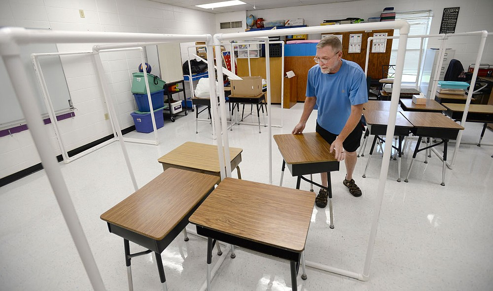 Wayne Ramsey, a second-grade teacher at West Fork Elementary School, arranges desks Friday, July 31, 2020, while constructing barriers to keep students safe while in his classroom at West Fork Elementary School. Visit nwaonline.com/200801Daily/ for today's photo gallery. (NWA Democrat-Gazette/Andy Shupe)