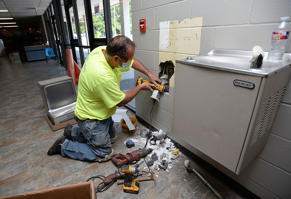 Matt Rhodes, owner of Rhodes Plumbing in West Fork, works to relocate electrical and water service in a wall in Dee Lee Gymnasium as he and his son, Curtis, change water fountains in all of the school buildings to ones that include a touchless water bottle filler Thursday, Aug. 6, 2020, as the school buildings are modified to meet covid-19 safety standards ahead of the first day of school. Visit nwaonline.com/200807Daily/ for today's photo gallery. (NWA Democrat-Gazette/Andy Shupe)