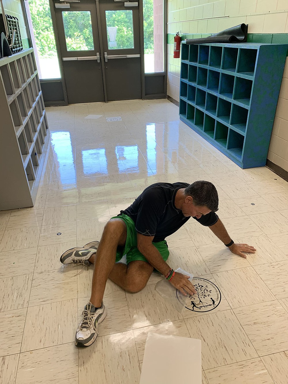 Alan Barton, longtime Greenland Elementary School principal, applies decals to the floor to help students with social distancing Thursday, Aug. 6, 2020, as he and his staff prepare the school to meet social-distancing and other covid-19 standards ahead of the first day of school. Visit nwaonline.com/200807Daily/ for today's photo gallery. (NWA Democrat-Gazette/Andy Shupe)
