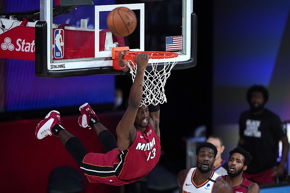 Miami Heat's Bam Adebayo (13) dunks over Phoenix Suns' Deandre Ayton during the second half of an NBA basketball game, Saturday, Aug. 8, 2020 in Lake Buena Vista, Fla. (AP Photo/Ashley Landis, Pool)