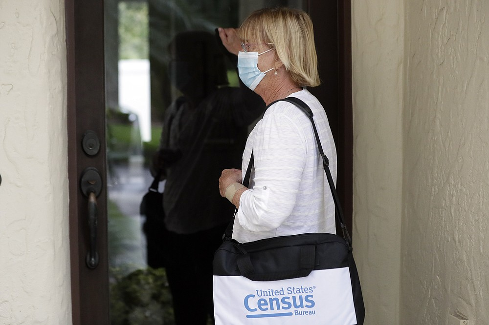 A census taker knocks on the door of a residence Tuesday, Aug. 11, 2020, in Winter Park, Fla. A half-million census takers head out en mass this week to knock on the doors of households that haven't yet responded to the 2020 census. (AP Photo/John Raoux)