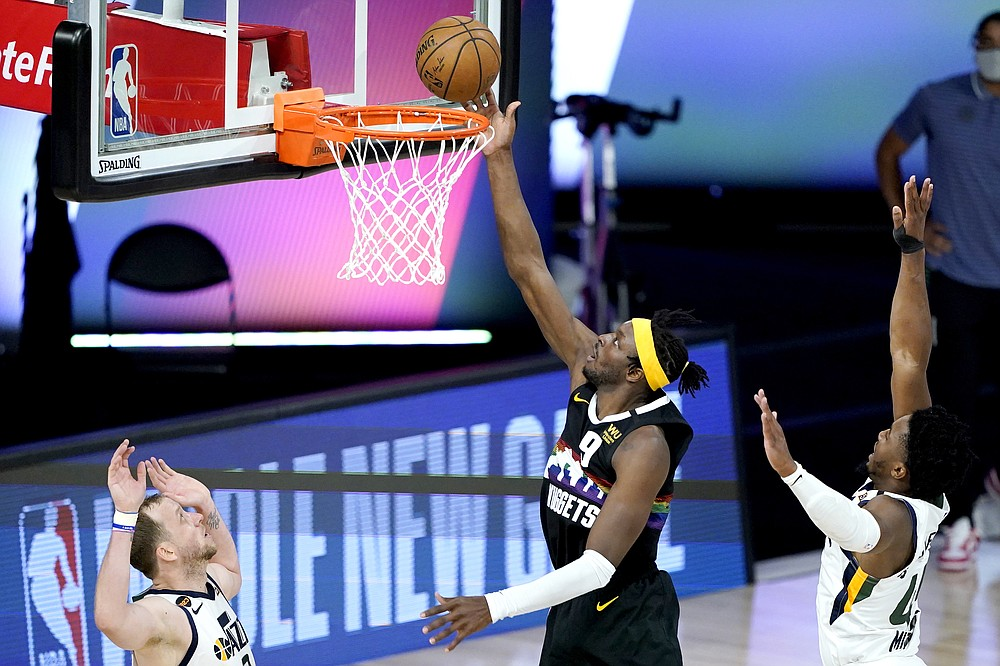 Denver Nuggets' Jerami Grant, center, scores a basket against Utah Jazz's Joe Ingles, left, and Donovan Mitchell during the second half of an NBA basketball first round playoff game, Monday, Aug. 17, 2020, in Lake Buena Vista, Fla. (AP Photo/Ashley Landis, Pool)