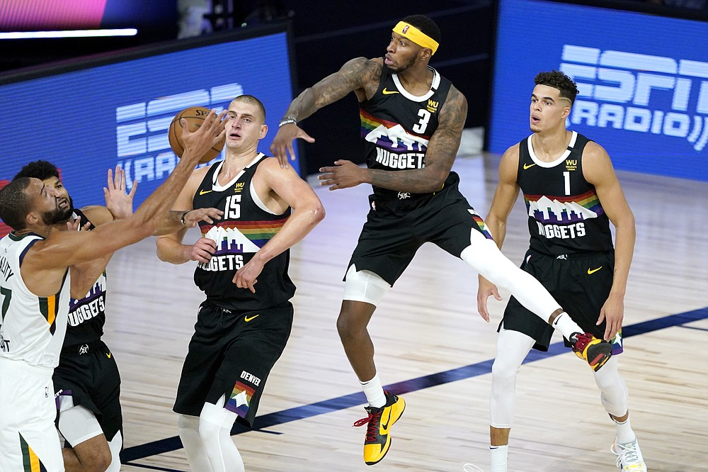 Denver Nuggets' Torrey Craig (3) tries to swat the ball away as Utah Jazz's Rudy Gobert, left, competes for a rebound against Nuggets' Nikola Jokic (15) during the first half of an NBA basketball first round playoff game, Monday, Aug. 17, 2020, in Lake Buena Vista, Fla. Nuggets' Michael Porter Jr. (1) looks on. (AP Photo/Ashley Landis, Pool)