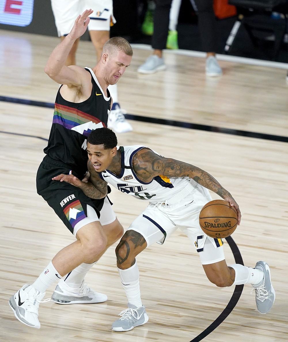Utah Jazz's Jordan Clarkson (00) drives against Denver Nuggets' Mason Plumlee (7) during the first half of an NBA basketball first round playoff game, Monday, Aug. 17, 2020, in Lake Buena Vista, Fla. (AP Photo/Ashley Landis, Pool)