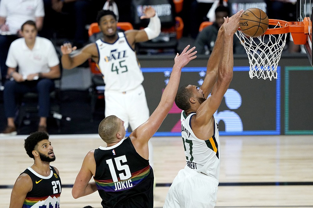 Utah Jazz's Rudy Gobert, right, misses a dunk against Denver Nuggets' Nikola Jokic (15) during the second half of an NBA basketball first round playoff game, Monday, Aug. 17, 2020, in Lake Buena Vista, Fla. Nuggets' Jamal Murray (27) and Jazz's Donovan Mitchell (45) look on during the play. (AP Photo/Ashley Landis, Pool)