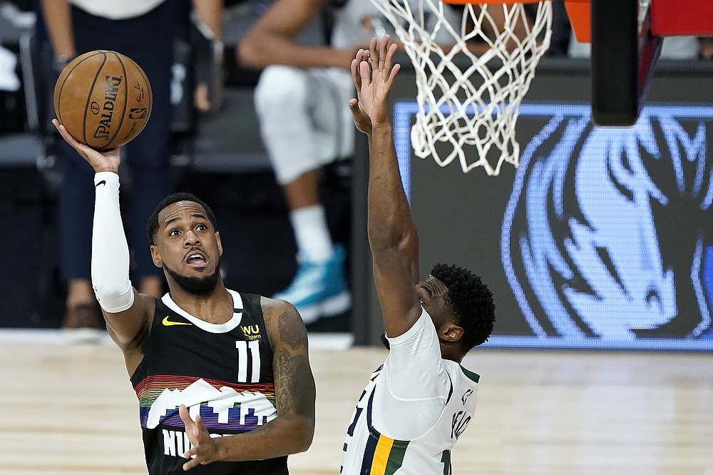 Denver Nuggets' Monte Morris (11) goes up for a shot against Utah Jazz's Emmanuel Mudiay during the first half of an NBA basketball first round playoff game, Monday, Aug. 17, 2020, in Lake Buena Vista, Fla. (AP Photo/Ashley Landis, Pool)