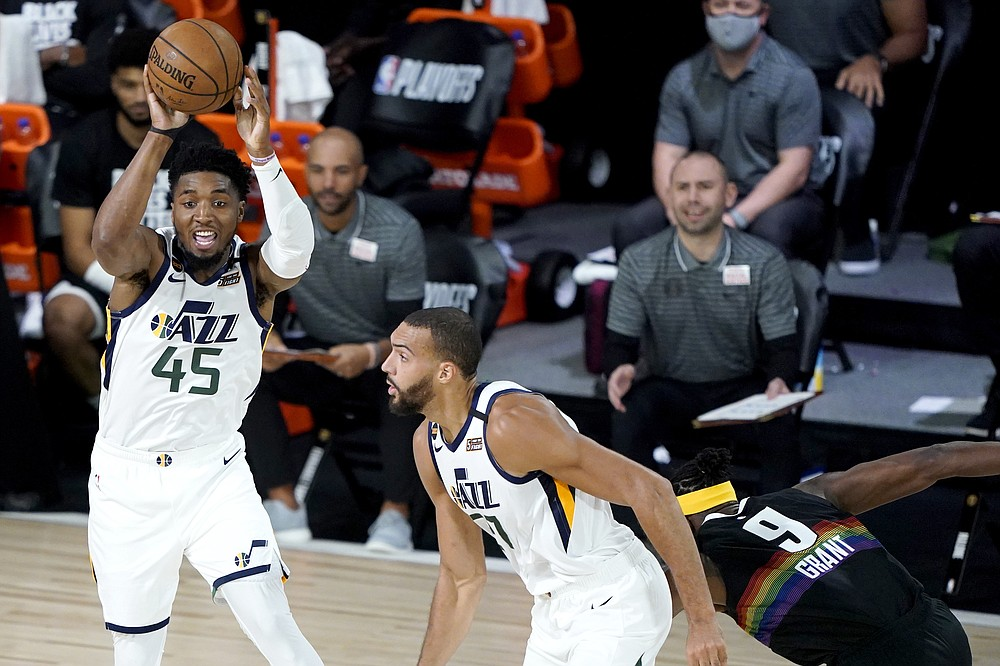 Utah Jazz's Donovan Mitchell (45) passes the ball as teammate Rudy Gobert, center, and moves up court against Denver Nuggets' Jerami Grant (9) during the first half of an NBA basketball first round playoff game, Monday, Aug. 17, 2020, in Lake Buena Vista, Fla. (AP Photo/Ashley Landis, Pool)