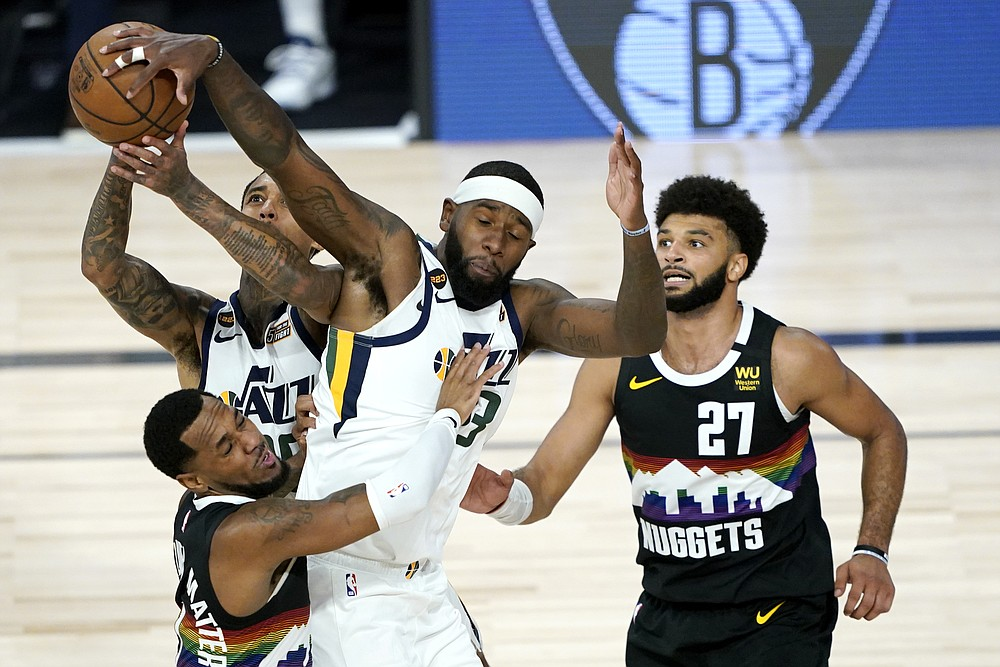 Utah Jazz's Jordan Clarkson, back, competes for a rebound with teammate Royce O'Neale, right, and Denver Nuggets' Monte Morris, left, during overtime in an NBA basketball first round playoff game, Monday, Aug. 17, 2020, in Lake Buena Vista, Fla. Nuggets' Jamal Murray (27) looks on. The Nuggets won 135-125 in overtime. (AP Photo/Ashley Landis, Pool)