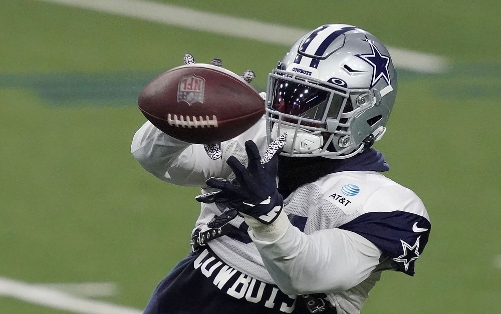 Dallas Cowboys running back Ezekiel Elliott (21) reaches for a pass during an NFL football training camp practice in Frisco, Texas, Tuesday, Aug. 18, 2020. (AP Photo/LM Otero)