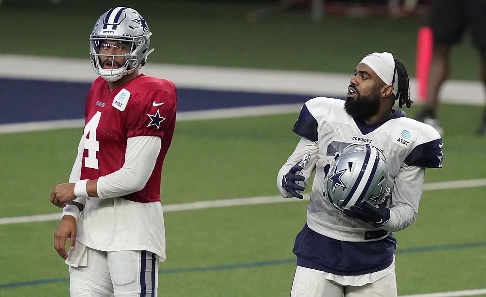 Dallas Cowboys quarterback Dak Prescott (4) and running back Ezekiel Elliott (21) start to line up for a drill during an NFL football training camp in Frisco, Texas, Monday, Aug. 17, 2020. (AP Photo/LM Otero)