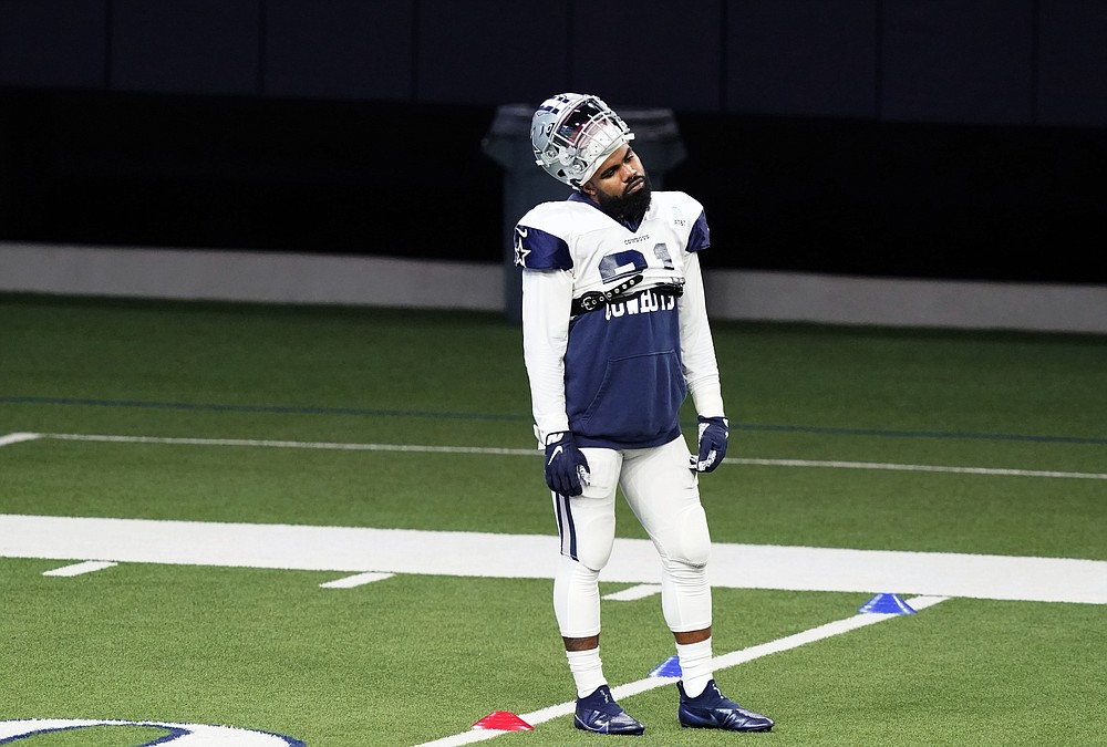 Dallas Cowboys running back Ezekiel Elliott (21) stands on the field during an NFL football training camp in Frisco, Texas, Tuesday, Aug. 18, 2020. (AP Photo/LM Otero)