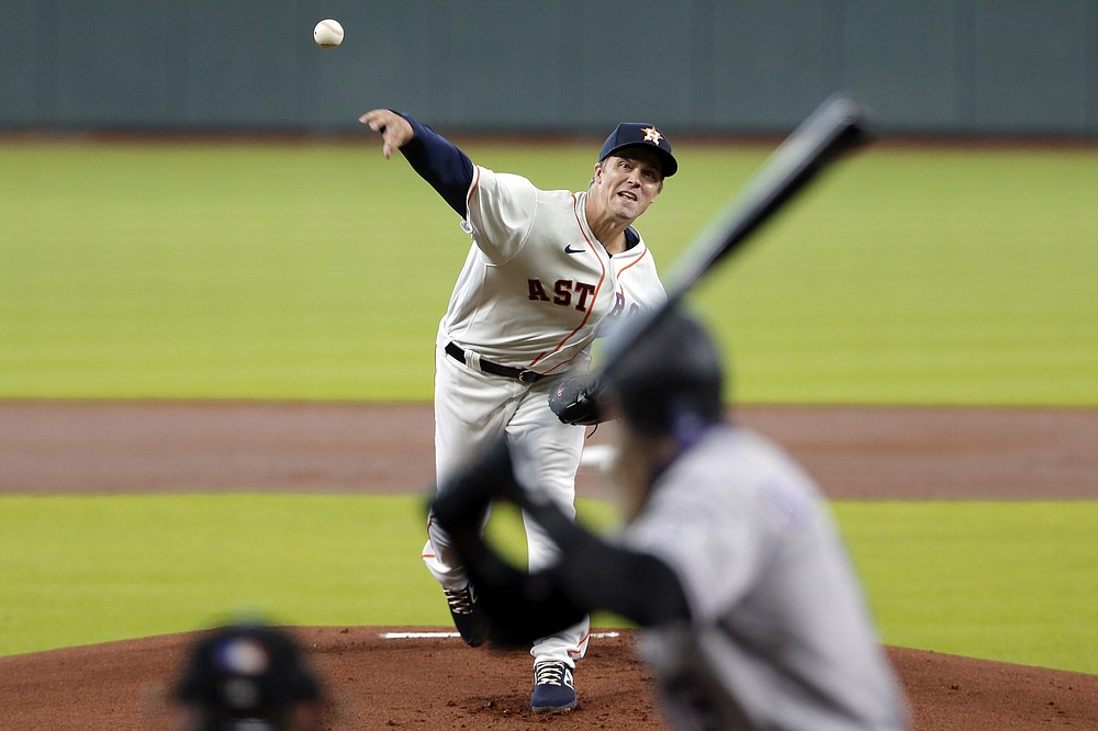 Houston Astros starting pitcher Zack Greinke, top, throws against Colorado Rockies Charlie Blackmon, right, during the first inning of a baseball game Tuesday, Aug. 18, 2020, in Houston. (AP Photo/Michael Wyke)