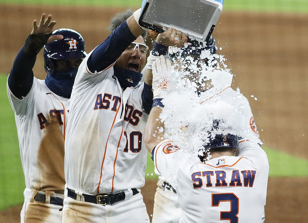 The Houston Astros' Myles Straw receives an ice bucket shower from Yuli Gurriel after hitting a walk-off single in the bottom of the eleventh inning against the Colorado Rockies on Tuesday, Aug. 18, 2020, at Minute Maid Park. (Kevin M. Cox/The Galveston County Daily News via AP)