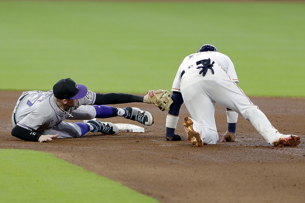 Colorado Rockies shortstop Trevor Story, left, makes the tag for the out at second base on Houston Astros Yuli Gurriel during the fourth inning of a baseball game Tuesday, Aug. 18, 2020, in Houston. (AP Photo/Michael Wyke)