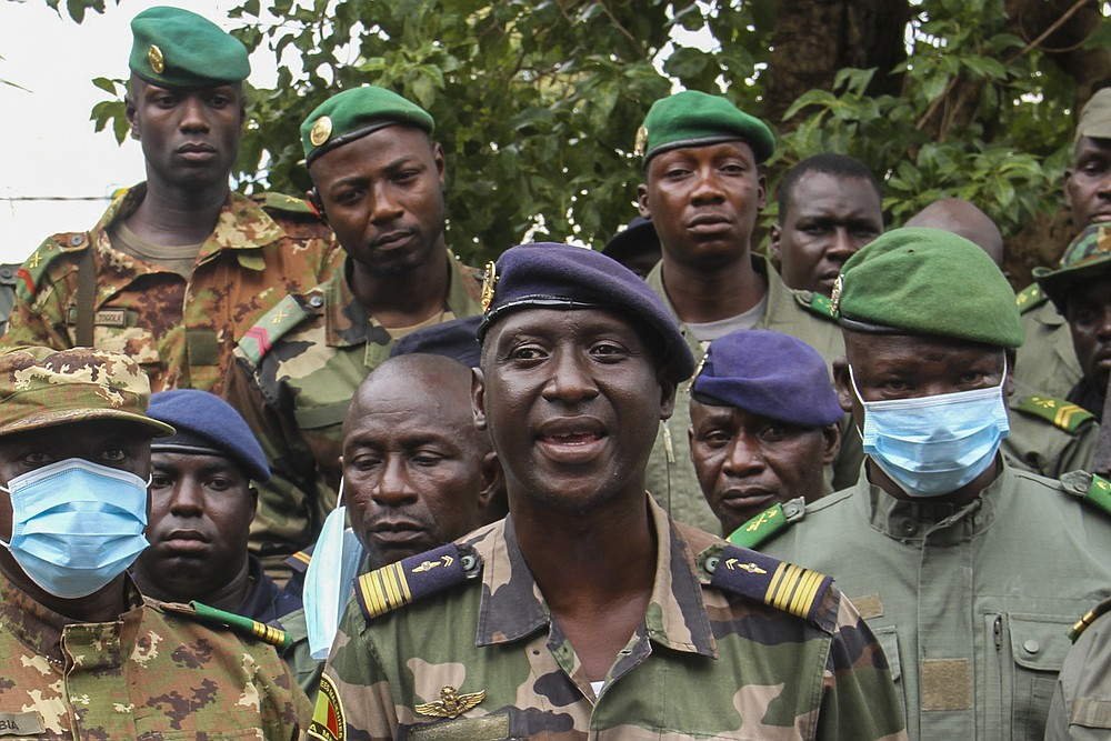 Colonel-Major Ismael Wague, centre, spokesman for the soldiers identifying themselves as National Committee for the Salvation of the People, speaks during a press conference at Camp Soudiata in Kati, Mali, Wednesday, Aug. 19, 2020, one day after President Ibrahim Boubacar Keita was forced to resign in a military coup. The military takeover was swiftly condemned by the international community, despite promesses of new elections. (AP Photo/Arouna Sissoko)