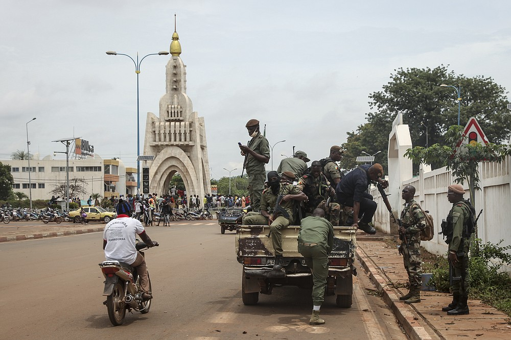 Security forces ride in a truck in the capital Bamako, Mali Wednesday, Aug. 19, 2020. The Malian soldiers who forced President Ibrahim Boubacar Keita to resign in a coup promised early Wednesday to organize new elections after their takeover was swiftly condemned by the international community. (AP Photo/Baba Ahmed)