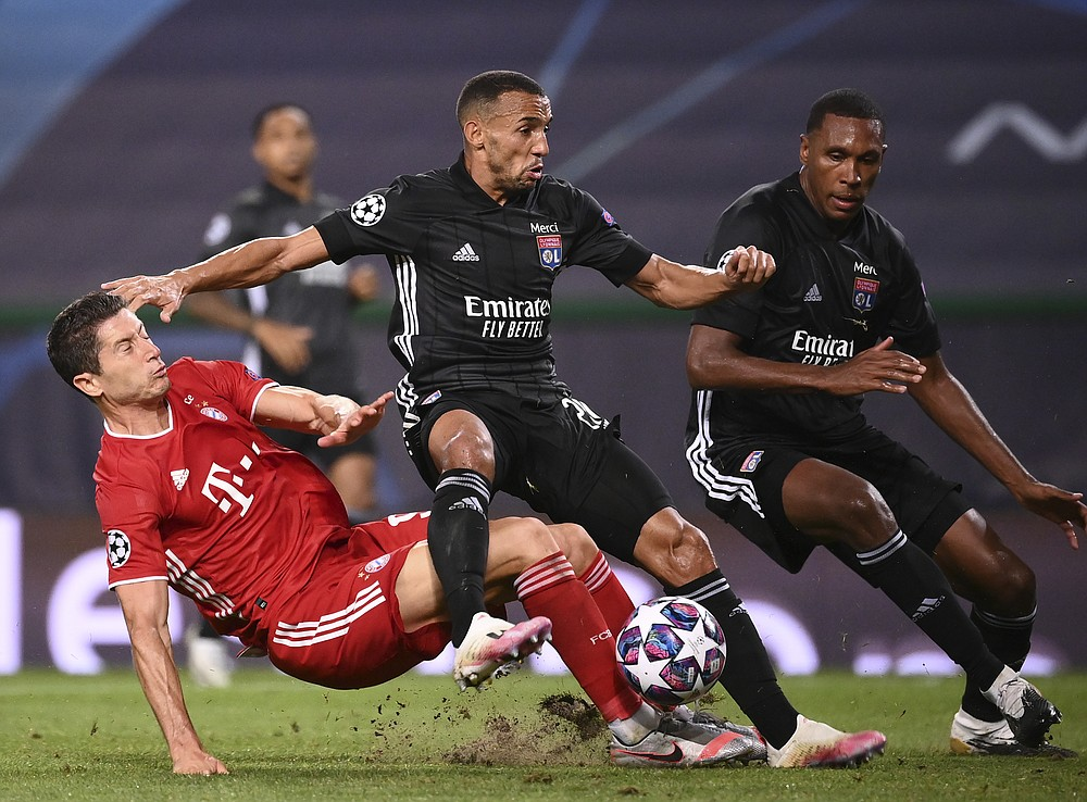 Lyon's Marcal, centre, duels for the ball with Bayern's Robert Lewandowski during the Champions League semifinal soccer match between Lyon and Bayern at the Jose Alvalade stadium in Lisbon, Portugal, Wednesday, Aug. 19, 2020. (Franck Fife/Pool via AP)
