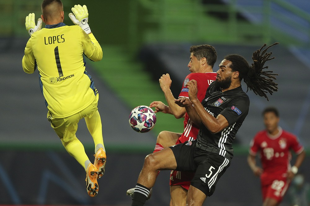 Lyon's Lucas Tousart, right, and Lyon's goalkeeper Anthony Lopes try to stop Bayern's Robert Lewandowski during the Champions League semifinal soccer match between Lyon and Bayern Munich at the Jose Alvalade stadium in Lisbon, Portugal, Wednesday, Aug. 19, 2020. (Miguel A. Lopes/Pool via AP)