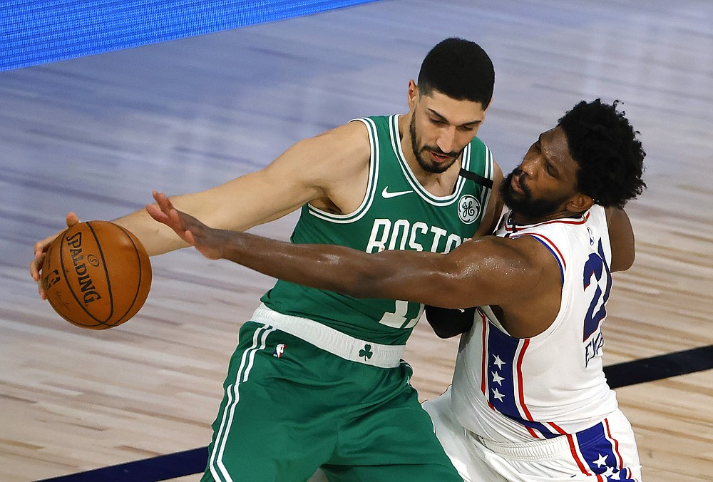 Philadelphia 76ers' Joel Embiid, right, reaches for a steal against Boston Celtics' Enes Kanter during the third quarter of Game 2 of an NBA basketball first-round playoff series, Wednesday, Aug. 19, 2020, in Lake Buena Vista, Fla. (Kevin C. Cox/Pool Photo via AP)