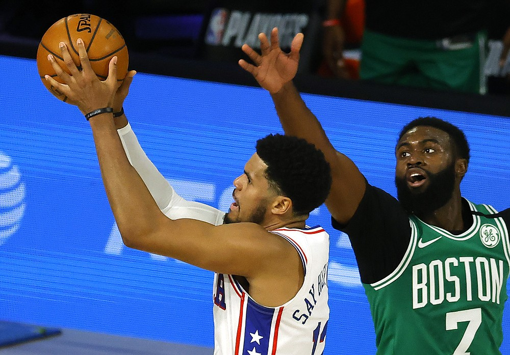 Tobias Harris, left, of the Philadelphia 76ers goes up for a shot against Jaylen Brown, right, of the Boston Celtics during the first half of Game 2 of an NBA basketball first-round playoff series, Wednesday, Aug. 19, 2020, in Lake Buena Vista, Fla. (Kevin C. Cox/Pool Photo via AP)
