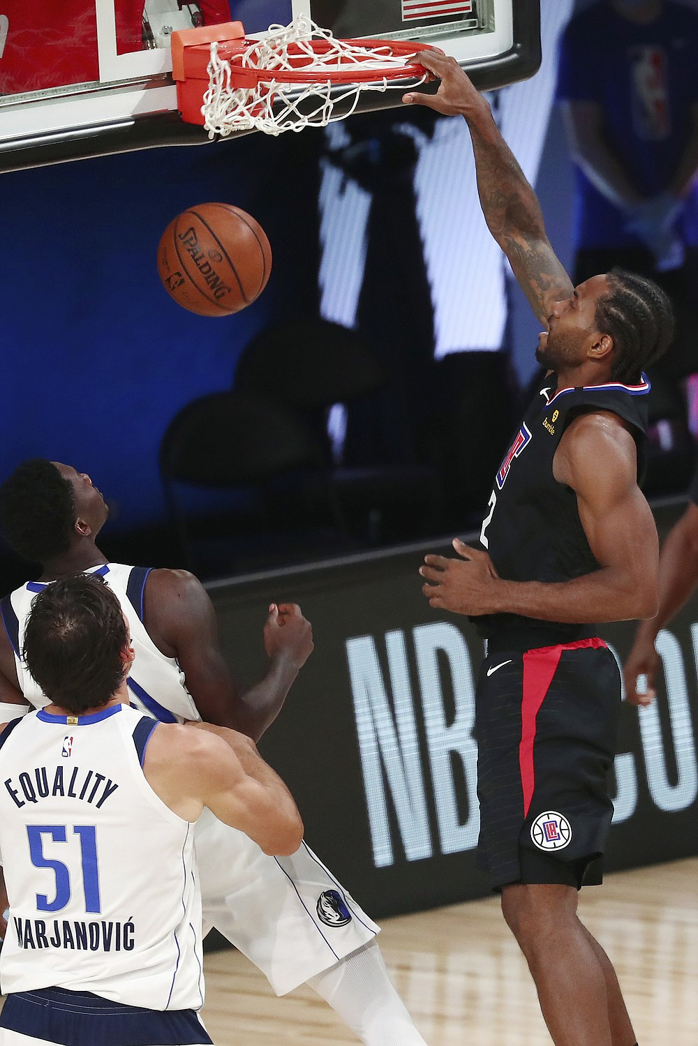 Los Angeles Clippers forward Kawhi Leonard dunks over Dallas Mavericks center Boban Marjanovic (51) and forward Dorian Finney-Smith during the second half of Game 2 of an NBA basketball basketball first-round playoff series, Wednesday, Aug. 19, 2020, in Lake Buena Vista, Fla. (Kim Klement/Pool Photo via AP)