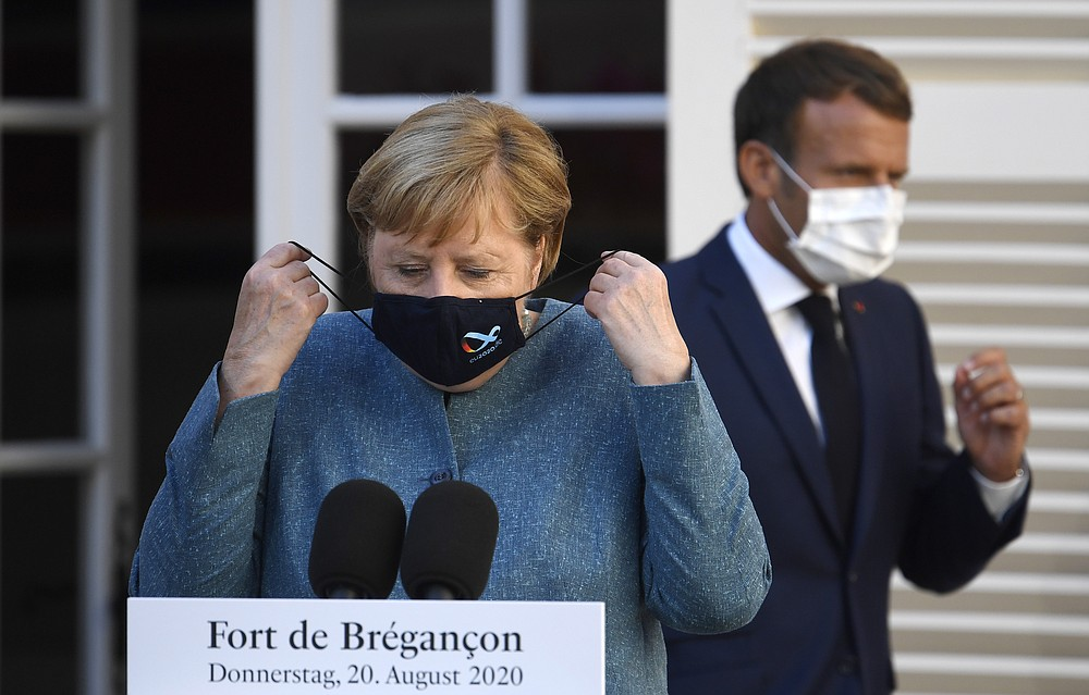 German Chancellor Angela Merkel, left, and French President Emmanuel Macron arrives for a press conference at the Fort de Bregancon, southern France, Thursday, Aug. 20, 2020. The leaders of Germany and France are meeting Thursday at a Mediterranean retreat for talks on how to resuscitate Europe's economy without causing a new virus crisis, and on a growing number of global hot spots. (Christophe Simon/Pool Photo via AP)