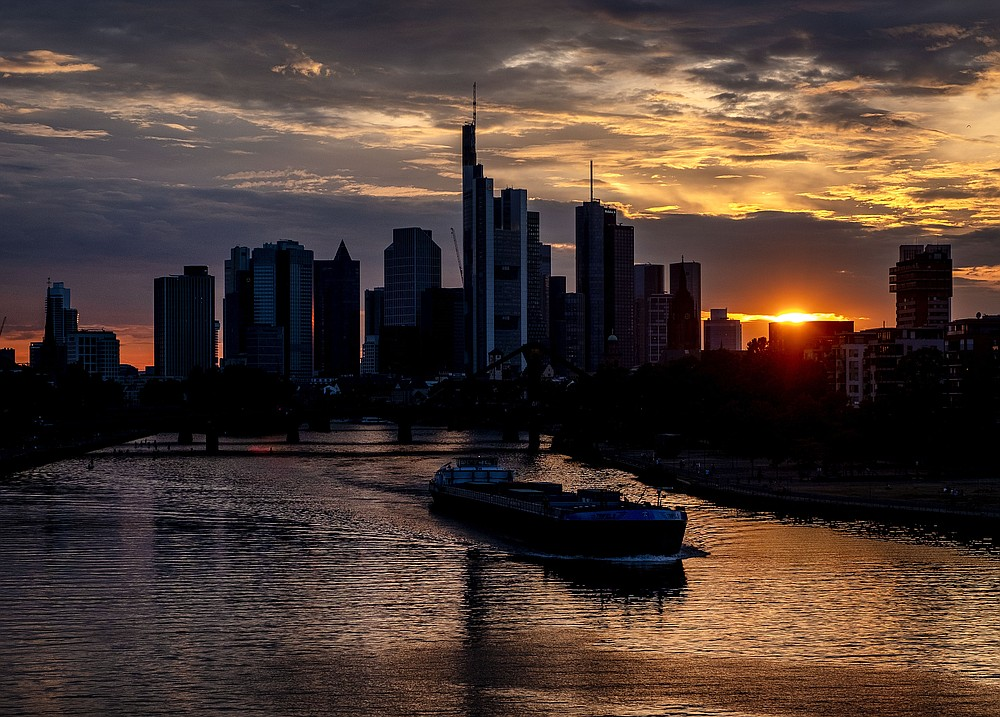 A cargo vessel cruises on the river Main with the buildings of the banking district in background in Frankfurt, Germany, after sunset on Friday, Aug. 14, 2020. (AP Photo/Michael Probst)