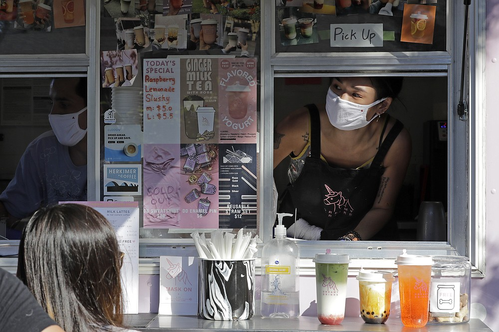 Kaye Fan, right, calls out orders as she works in her Dreamy Drinks food truck, Monday, Aug. 10, 2020, near the suburb of Lynnwood, Wash., north of Seattle. Long seen as a feature of city living, food trucks are now finding customers in the suburbs during the coronavirus pandemic as people are working and spending most of their time at home. (AP Photo/Ted S. Warren)