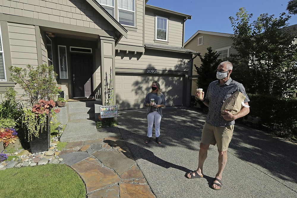 Julie and Greg Schwab stand in front of their home after walking back with their orders from the Dreamy Drinks and YS Street Food food trucks, Monday, Aug. 10, 2020, near the suburb of Lynnwood, Wash., north of Seattle. In June, Julie Schwab started organizing a regular schedule to bring food trucks to their neighborhood as a way to both help small businesses and give families staying at home during the coronavirus pandemic different options for meals. Long seen as a feature of city living, food trucks are now finding customers in the suburbs during the coronavirus pandemic as people are working and spending most of their time at home. (AP Photo/Ted S. Warren)