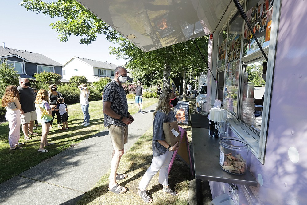 Julie and Greg Schwab wait to order from the Dreamy Drinks food truck, Monday, Aug. 10, 2020, near the suburb of Lynnwood, Wash., north of Seattle. In June, Julie Schwab started organizing a regular schedule to bring food trucks to their neighborhood as a way to both help small businesses and give families staying at home during the coronavirus pandemic different options for meals. Long seen as a feature of city living, food trucks are now finding customers in the suburbs during the coronavirus pandemic as people are working and spending most of their time at home. (AP Photo/Ted S. Warren)