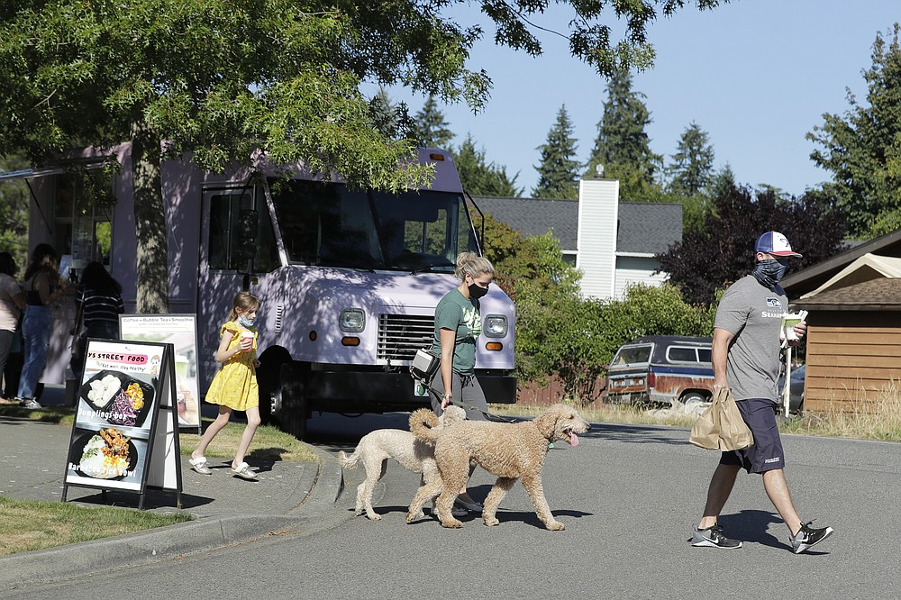 Bobby Price, right, and Catherine Vogt, center, walk with Catherine's daughter Avery, 8, and their dogs after ordering food and drinks from the YS Street Food and Dreamy Drinks food trucks, Monday, Aug. 10, 2020, near the suburb of Lynnwood, Wash., north of Seattle. Long seen as a feature of city living, food trucks are now finding customers in the suburbs during the coronavirus pandemic as people are working and spending most of their time at home. (AP Photo/Ted S. Warren)