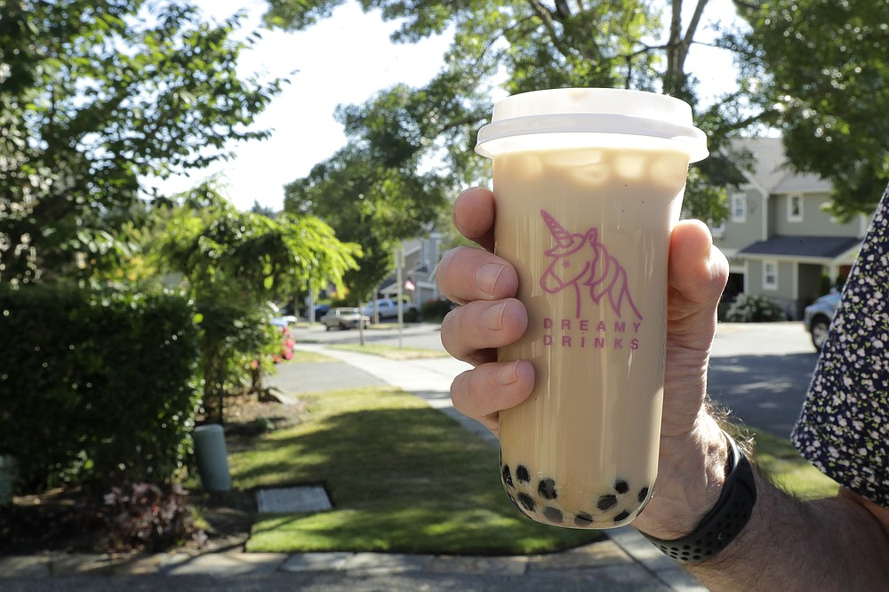 Greg Schwab holds a boba tea he ordered from the Dreamy Drinks food truck, Monday, Aug. 10, 2020, near the suburb of Lynnwood, Wash., north of Seattle. In June, Greg's wife Julie Schwab started organizing a regular schedule to bring food trucks to their neighborhood as a way to both help small businesses and give families staying at home during the coronavirus pandemic different options for meals. Long seen as a feature of city living, food trucks are now finding customers in the suburbs during the coronavirus pandemic as people are working and spending most of their time at home. (AP Photo/Ted S. Warren)