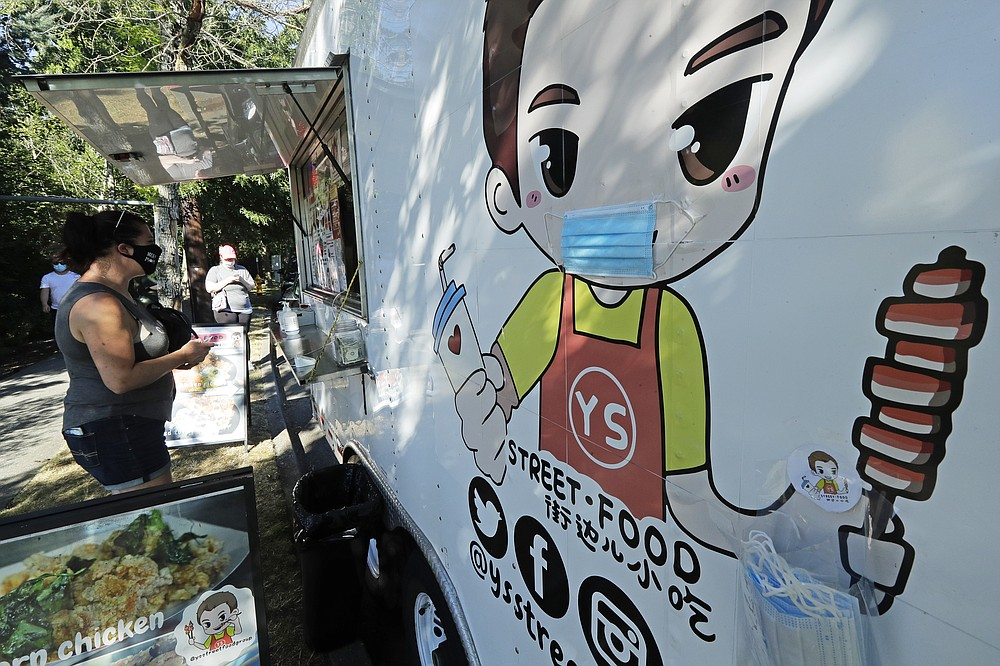 A customer orders from the YS Street Food food truck, Monday, Aug. 10, 2020, near the suburb of Lynnwood, Wash., north of Seattle. Long seen as a feature of city living, food trucks are now finding customers in the suburbs during the coronavirus pandemic as people are working and spending most of their time at home. (AP Photo/Ted S. Warren)