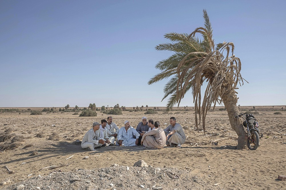 "55-year-old Egyptian farmer Makhluf Abu Kassem, center, sits with farmers under shade of a dried up palm tree surrounded by barren wasteland that was once fertile and green, in Second Village, Qouta town, Fayoum, Egypt, Wednesday, Aug. 5, 2020. Abu Kassem fears that a dam Ethiopia is building on the Blue Nile, the Nile's main tributary, could add to the severe water shortages already hitting his village if no deal is struck to ensure a continued flow of water. ""The dam means our death,"" he said. (AP Photo/Nariman El-Mofty)"