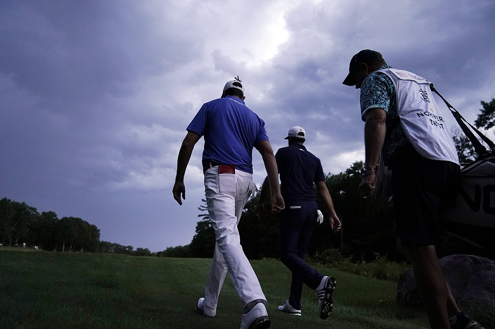 Harris English, left, and Dustin Johnson, center, walk up the fairway on the 18th hole during the final round of the Northern Trust golf tournament at TPC Boston, Sunday, Aug. 23, 2020, in Norton, Mass. (AP Photo/Charles Krupa)