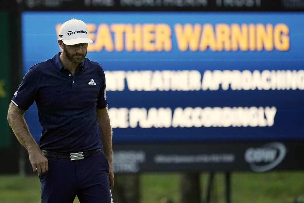 Dustin Johnson walks off the course after play was stopped while he was on the 17th fairway during the final round of the Northern Trust golf tournament at TPC Boston, Sunday, Aug. 23, 2020, in Norton, Mass. (AP Photo/Charles Krupa)