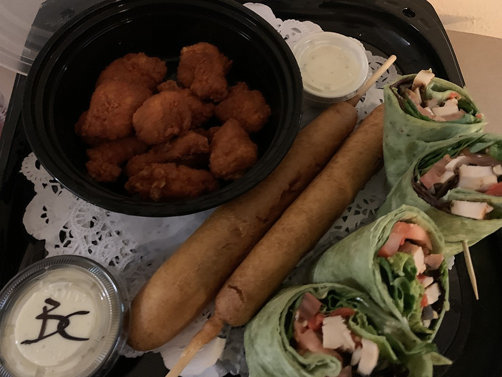 Arena food from Simmons Bank Arena includes (from left) buffalo-style boneless wings with blue cheese dressing, corn dogs and a chicken Caesar salad wrap.  (Arkansas Democrat-Gazette/Eric E. Harrison)