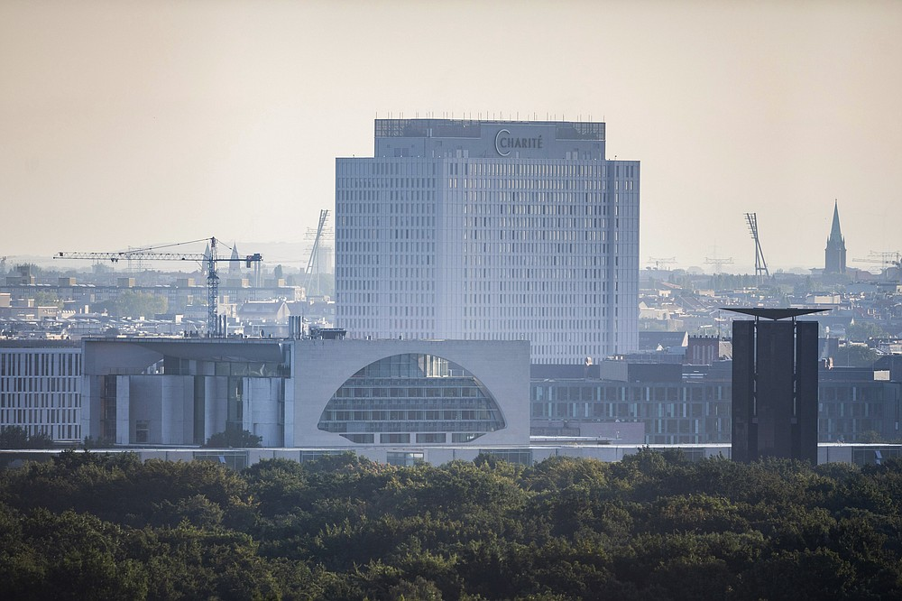 The central building of Charite hospital where Russian dissident Alexei Navalny is treating, seen behind the Chancellery in Berlin, Tuesday, Aug. 25, 2020. German Chancellor Angela Merkel is calling on Russian authorities to conduct a full investigation of the poisoning of dissident Alexei Navalny and to bring those responsible to justice. (Christoph Soeder/dpa via AP)