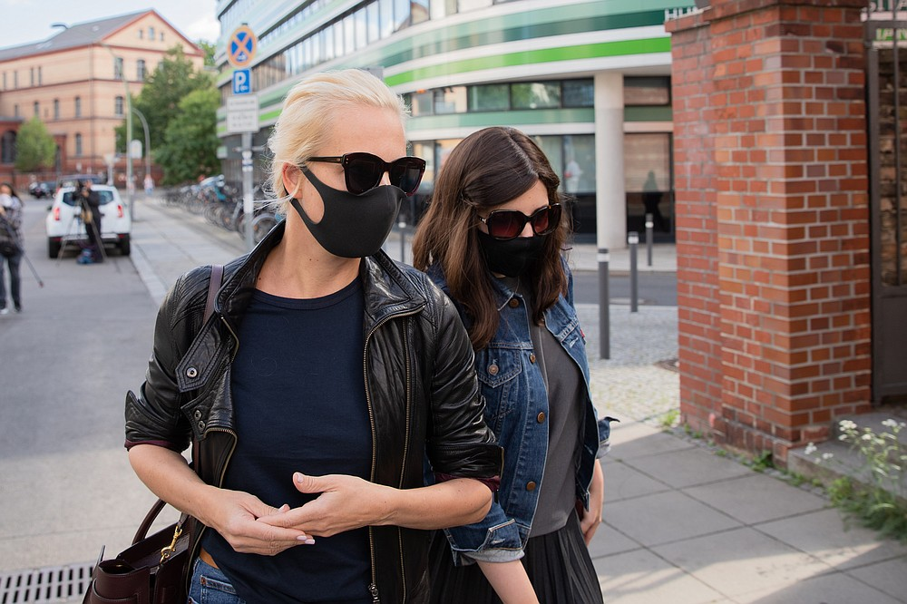The wife of the Russian oppositional Alexei Navalny, Julia, left,  arrives at the Berlin Charite Tuesday, Aug.25, 2020.  The Russian oppositional Navalny is treated in the clinic. Doctors at the Berlin Charité Hospital assume that the Kremlin critic has been poisoned. (Christoph Soeder/dpa via AP)