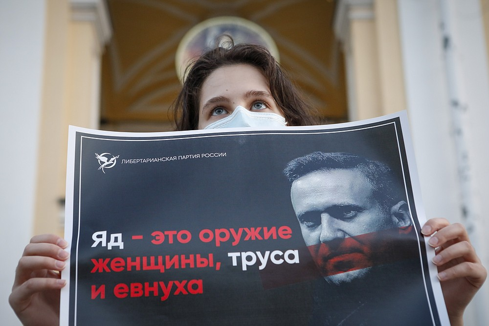 """FILE - In this Thursday, Aug. 20, 2020 file photo, a protester stands holds a poster reads """"poison is the weapon of a woman, a coward and a eunuch!"""" during a picket in support of Russian opposition leader Alexei Navalny in the center of St. Petersburg, Russia. The German hospital treating Navalny says tests indicate that he was poisoned. The Charité hospital said in a statement Monday, Aug. 24, 2020 that the team of doctors who have been examining Navalny since he was admitted Saturday have found the presence of """"cholinesterase inhibitors"""" in his system. Cholinesterase inhibitors are a broad range of substances that are found in several drugs, but also pesticides and nerve agents. (AP Photo/Elena Ignatyeva, File)"""
