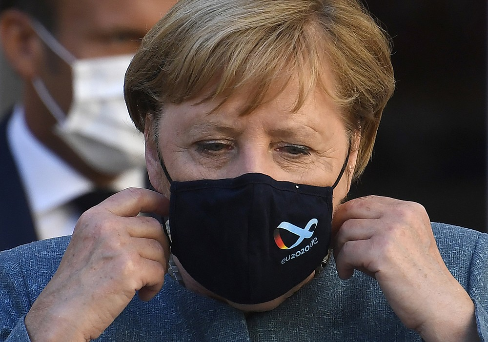 FILE - In this file photo dated Thursday, Aug. 20, 2020, German Chancellor Angela Merkel takes her mask off as she arrives for a press conference at the Fort de Bregancon, southern France.  Merkel said Monday Aug. 24, 2020, that in view of Alexei Navalny's prominent role in Russia's political opposition, that Russian authorities should conduct a full investigation of the alleged poisoning of the dissident, and to bring those responsible to justice. (Christophe Simon/Pool FILE via AP)