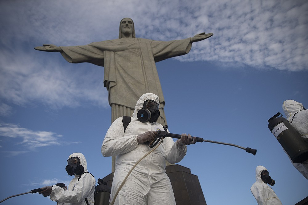 Soldiers disinfect the Christ the Redeemer site, currently closed due to the coronavirus pandemic in Rio de Janeiro, Brazil, Thursday, Aug. 13, 2020. The United Nations Secretary-General Antonio Guterres on Tuesday, Aug. 25, 2020, said the global tourism industry has been devastated by the coronavirus pandemic, with $320 billion lost in exports in the first five months of the year and more than 120 million jobs at risk. (AP Photo/Silvia Izquierdo, File)