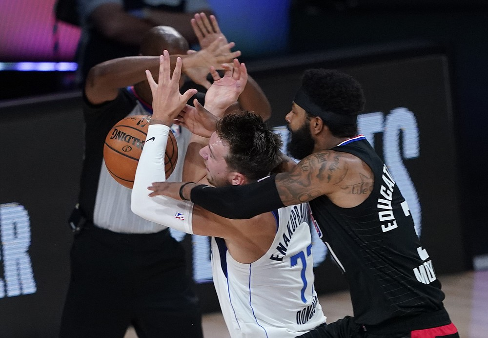 Dallas Mavericks' Luka Doncic (77) is fouled by Los Angeles Clippers' Marcus Morris Sr. during the first half of an NBA first round playoff game Sunday, Aug. 30, 2020, in Lake Buena Vista, Fla. (AP Photo/Ashley Landis)